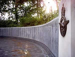 The sun sets behind the memorial wall