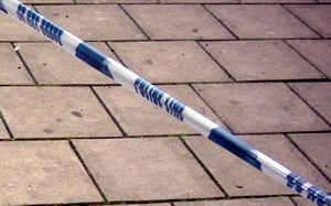 Police tape against paving stones